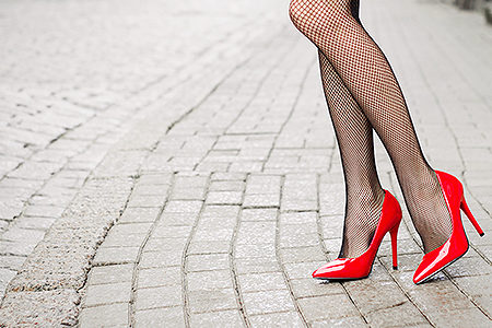 Woman wearing red high heel shoes in city